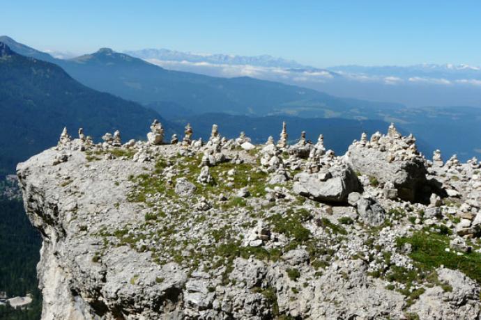 Turyści w Dolomitach lubią układać kopczyki... W tle na horyzoncie Alpy.