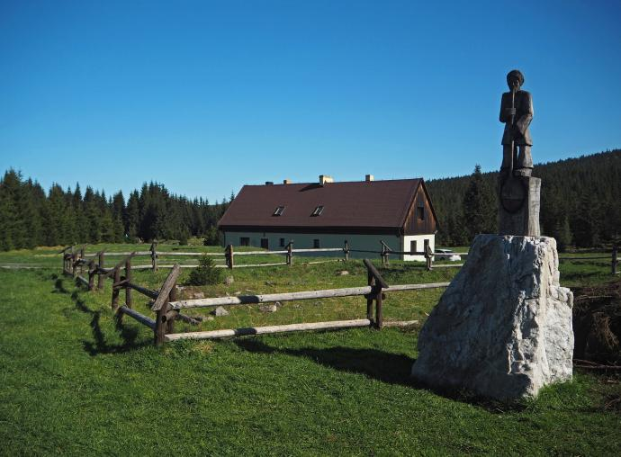 Dawny dom hutników oraz drewniana rzeźba im poświęcona.