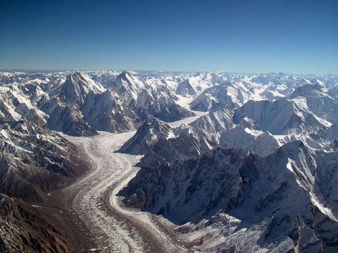 Ryc. 6. Lodowiec Baltoro z powietrza. W tle: Concordia (połączenie dwóch dużych lodowców dopływowych z lewej i prawej strony zdjęcia) i ośmiotysięczniki Gasherbrum. Fot. Guilhem Vellut, Wikimedia, CC-BY-SA-2.0.