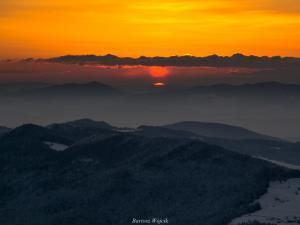 Słońce się wynurza i odbija w chmurach.