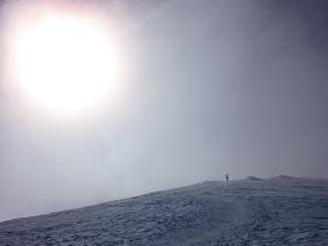 Samotny człowiek w blasku słońca, w cieniu chmur