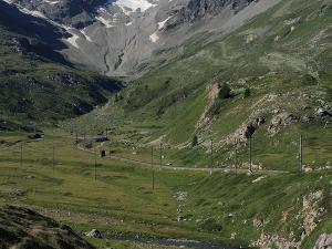 Jadę szosą w pobliżu torów najbardziej spektakularnej podróży pociągiem przez Alpy - Bernina Express.