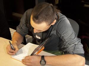 Adam Bielecki podpisuje książkę